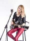 Ο ξανθός κιθαρίστας κοριτσιών με την ηλεκτρική κιθάρα μαθαίνει το τραγούδι παιχνιδιών, κάθεται στην καρέκλα, τραγουδά στο αναδρομ στοκ φωτογραφία