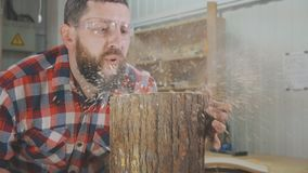 Ο ξυλουργός ατόμων σε ένα πουκάμισο με μια γενειάδα φυσά τα ξέσματα στο εργαστήριο Στοκ εικόνα με δικαίωμα ελεύθερης χρήσης