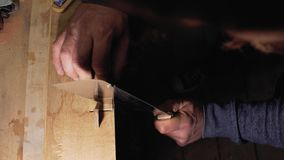 Ο ξυλουργός βιοτεχνών εφαρμόζει μια περικοπή σε μια ξύλινη χτένα με μια κινηματογράφηση σε πρώτο πλάνο πριονιών χεριών 4k ένας βι απόθεμα βίντεο