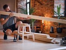 Ο ξυλουργός ελέγχει τους πίνακες σε ένα δωμάτιο σοφιτών Στοκ Εικόνες