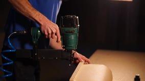 Ο ξυλουργός ενισχύει μια ξύλινη σανίδα στη βάση των επίπλων με stapler απόθεμα βίντεο