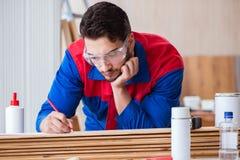Ο ξυλουργός επισκευαστών yooung που εργάζεται με τη ζωγραφική χρωμάτων Στοκ Εικόνα