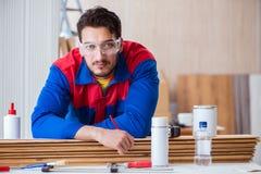 Ο ξυλουργός επισκευαστών yooung που εργάζεται με τη ζωγραφική χρωμάτων Στοκ Φωτογραφίες