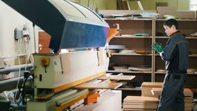 Ο ξυλουργός εργαζομένων χειρίζεται τα ξύλινα μέρη επίπλων στη μηχανή στο εργοστάσιο φιλμ μικρού μήκους