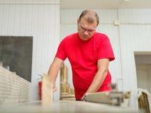 Ο ξυλουργός ισοπεδώνει το φραγμό ξυλείας στον εργασιακό χώρο Στοκ εικόνες με δικαίωμα ελεύθερης χρήσης