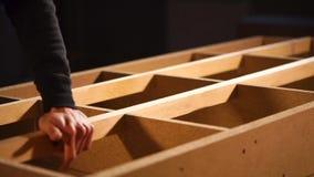 Ο ξυλουργός καθορίζει την ξύλινη ακτίνα σε ένα σφάγιο του καναπέ στη συγκέντρωση του καταστήματος απόθεμα βίντεο