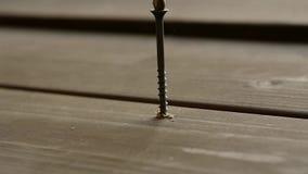Ο ξυλουργός καθορίζει το ξύλινο πάτωμα με τις βίδες με ένα κατσαβίδι o φιλμ μικρού μήκους