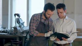 Ο ξυλουργός και τα boos του που συζητούν την ξυλουργική στο εργαστήριο στοκ εικόνα με δικαίωμα ελεύθερης χρήσης