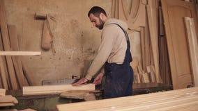 Ο ξυλουργός κόβει τις πλευρές του ξύλινου φραγμού στο κυκλικό πριόνι Ξύλινα ξέσματα Το εργαστήριο γεμίζουν με φιλμ μικρού μήκους