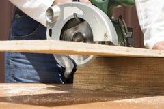 Ο ξυλουργός κόβει τον πίνακα με ένα χειρωνακτικό ηλεκτρικό πριόνι Στοκ φωτογραφία με δικαίωμα ελεύθερης χρήσης