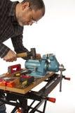 Ο ξυλουργός με το εργαλείο σε μια άσπρη ανασκόπηση. Στοκ εικόνα με δικαίωμα ελεύθερης χρήσης