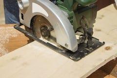 Ο ξυλουργός πετσοκόβει τον πίνακα χρησιμοποιώντας ένα ηλεκτρικό πριόνι στοκ εικόνες με δικαίωμα ελεύθερης χρήσης