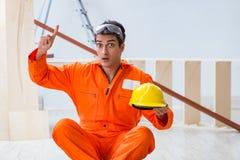 Ο ξυλουργός που φορά κίτρινο hardhat στο εργαστήριο αναδόχων Στοκ Εικόνες