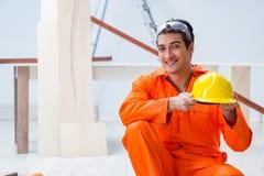 Ο ξυλουργός που φορά κίτρινο hardhat στο εργαστήριο αναδόχων Στοκ Φωτογραφίες