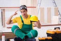 Ο ξυλουργός που φορά κίτρινο hardhat στο εργαστήριο αναδόχων Στοκ φωτογραφία με δικαίωμα ελεύθερης χρήσης