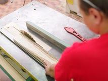 Ο ξυλουργός πριονίζει την ακτίνα ξυλείας σε ένα κυκλικό πριόνι Στοκ Φωτογραφία