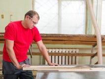 Ο ξυλουργός πριονίζει την ακτίνα ξυλείας σε ένα κυκλικό πριόνι Στοκ Εικόνες