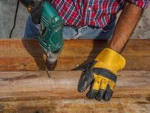 Ο ξυλουργός τρυπά μια τρύπα με ένα ηλεκτρικό τρυπάνι με τρυπάνι επάγγελμα, ασβέστιο Στοκ Φωτογραφίες