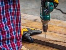 Ο ξυλουργός τρυπά μια τρύπα με ένα ηλεκτρικό τρυπάνι με τρυπάνι επάγγελμα, ασβέστιο Στοκ Εικόνα