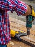Ο ξυλουργός τρυπά μια τρύπα με ένα ηλεκτρικό τρυπάνι με τρυπάνι επάγγελμα, ασβέστιο Στοκ Εικόνες