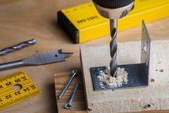 Ο ξυλουργός τρυπά μια τρύπα με ένα ηλεκτρικό τρυπάνι με τρυπάνι στοκ εικόνα