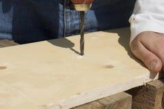 Ο ξυλουργός τρυπά μια τρύπα στον πίνακα με τρυπάνι Στοκ Εικόνες