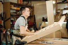 Ο ξυλουργός φέρνει την ξύλινη σανίδα στο εργαστήριο Άτομο με τη χάραξη του εξοπλισμού, στοκ φωτογραφίες