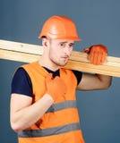 Ο ξυλουργός, woodworker, ισχυρός οικοδόμος στο σοβαρό πρόσωπο φέρνει την ξύλινη ακτίνα στον ώμο Ξύλινη έννοια υλικών άτομο μέσα στοκ φωτογραφία