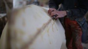 Ο ξυλουργός γυαλίζει μια ξύλινη βάρκα στο ναυπηγείο απόθεμα βίντεο