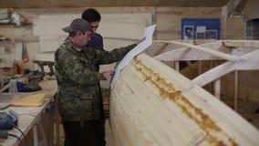 Ο ξυλουργός εξηγεί σε έναν συνάδελφο τις λεπτομέρειες του σχεδίου της βάρκας στο ναυπηγείο απόθεμα βίντεο