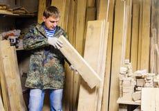 Ο ξυλουργός επιλέγει το ξύλο για να καταλάβει την αποθήκη εμπορευμάτων στοκ εικόνες