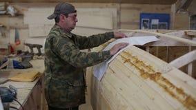 Ο ξυλουργός μελετά το σχέδιο της βάρκας στο ναυπηγείο φιλμ μικρού μήκους