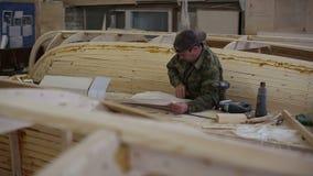 Ο ξυλουργός μελετά το σχέδιο της βάρκας στο ναυπηγείο απόθεμα βίντεο