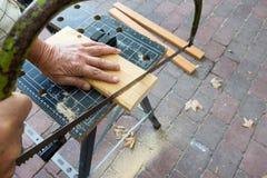Ο ξυλουργός που έχουν χάσει μια άκρη δάχτυλων πριονίζει Στοκ Εικόνες