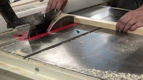 Ο ξυλουργός που εργάζεται στα πριόνια μηχανών ξυλουργικής πριονίζει τις κυκλοφορώντας ακτίνες στα ίδια κομμάτια vymerennye φιλμ μικρού μήκους