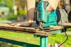 Ο ξυλουργός πριονίζει τη σανίδα στο πάρκο Στοκ εικόνα με δικαίωμα ελεύθερης χρήσης