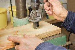Ο ξυλουργός τρυπά μια τρύπα στον πίνακα με τρυπάνι Στοκ φωτογραφία με δικαίωμα ελεύθερης χρήσης