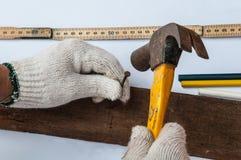Ο ξυλουργός χρησιμοποιεί το σφυρί και το καρφί στο ξύλο Στοκ Εικόνα