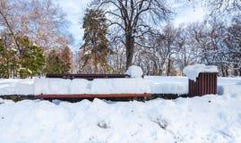 Ο ξύλινα πάγκος και τα απορρίματα ή τα παλιοπράγματα μπορούν στην οδό ή στο πάρκο που καλύπτεται με το χιόνι στη χειμερινή εποχή  στοκ εικόνες