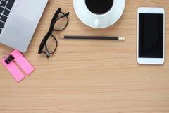 Ο ξύλινος πίνακας που λειτουργεί έχει έναν υπολογιστή και μια κούπα καφέ κοντά στο α στοκ εικόνα με δικαίωμα ελεύθερης χρήσης