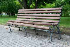 Ο ξύλινος σφυρηλατημένος πάγκος πάρκων, καφετής πάγκος με τα σφυρηλατημένα πόδια μετάλλων, κεραμίδια πεζοδρομίων, σταθμεύει το τε στοκ εικόνες