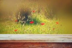 Ο ξύλινος αγροτικός πίνακας μπροστά από τις κόκκινες παπαρούνες ενάντια στον ουρανό με το φως εξερράγη φιλτραρισμένη την τρύγος ε Στοκ Εικόνες
