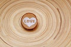 Ο ξύλινος κύκλος με μια χρωματισμένη καρδιά και η λέξη αγαπούν σε ένα ριγωτό υπόβαθρο τον ξύλινο δίσκο Τρόπος υποβάθρου Στοκ Εικόνες