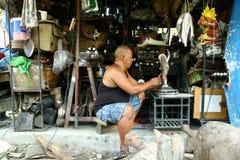 Ο ξύλινος τροχιστής βάζει τις τελευταίες πινελιές σε ένα διακοσμητικό ειδώλιο που πωλείται σε Dapitan Arcade στη Μανίλα, Φιλιππίν Στοκ φωτογραφία με δικαίωμα ελεύθερης χρήσης