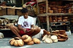 Ο ξύλινος τροχιστής βάζει τις τελευταίες πινελιές στα ξύλινα πιάτα που πωλούνται σε Dapitan Arcade στη Μανίλα, Φιλιππίνες Στοκ Φωτογραφία