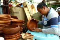 Ο ξύλινος τροχιστής βάζει τις τελευταίες πινελιές στα ξύλινα πιάτα που πωλούνται σε Dapitan Arcade στη Μανίλα, Φιλιππίνες Στοκ φωτογραφία με δικαίωμα ελεύθερης χρήσης
