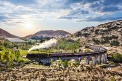 Οδογέφυρα σιδηροδρόμων Glenfinnan στη Σκωτία με το τραίνο ατμού Jacobite ενάντια στο ηλιοβασίλεμα πέρα από τη λίμνη στοκ εικόνες