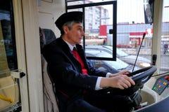 Ο οδηγός ενός υβριδικού trolleybus-λεωφορείου στη ρόδα Στοκ Φωτογραφία