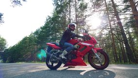 Ο οδηγός κάθεται στην κόκκινη μοτοσικλέτα απόθεμα βίντεο