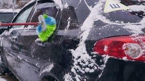 Ο οδηγός καθαρίζει το αυτοκίνητο από την κινηματογράφηση σε πρώτο πλάνο χιονιού απόθεμα βίντεο